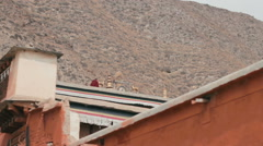 Stock Video Footage of Monks play a gong on the rooftops of Labrang Monastery