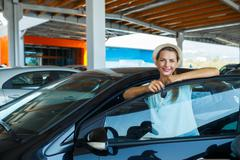 Young happy woman standing near a car with keys in hand - concept of buying a Stock Photos