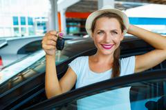 Young happy woman standing near a car with keys in hand - concept of buying a Kuvituskuvat