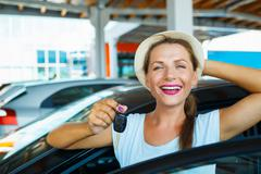 Young happy woman standing near a car with keys in hand - concept of buying a - stock photo