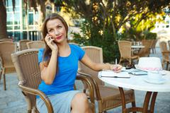 Candid image of a young pretty woman talking on the phone and makes notes in Stock Photos