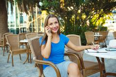 Candid image of a young pretty woman talking on the phone and makes notes in - stock photo