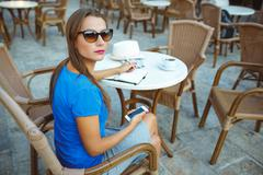 Stock Photo of Candid image of a young pretty woman using smartphone and makes notes in a no