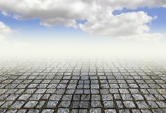 Old stone pavement and bright sky - stock photo
