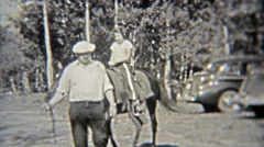 1937: Girl getting horse riding lessons through the forest. Stock Footage