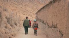 Tibetan Buddhist pilgrims circumambulate Labrang Monastery, Xiahe, China Stock Footage