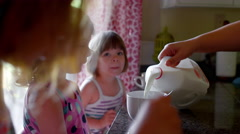 A mother pours milk into her daughters' cereal bowls - stock footage