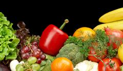 Group of different vegetables and fruits on black background - stock photo