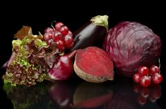 Group of purple vegetables and fruits on black background Stock Photos