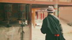 Tibetan Buddhist monks and pilgrims spin prayer wheels at Labrang Monastery - stock footage
