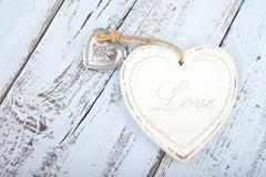 White heart with text Love on light blue wooden background Stock Photos