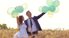 Wedding couple hugging and kissing outdoors in a field with balloons. Bride and - stock footage