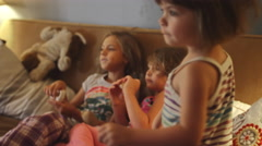 Little girls on a couch watching television and eating donuts Stock Footage