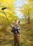 Happy little boy taking selfie stick picture Stock Photos