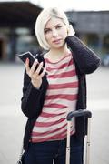 Woman using phone when traveling with public transport - stock photo