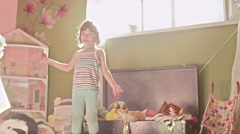 A cute little girl with a spoonful of peanut butter holds up toys from toy box Stock Footage