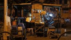 Man enjoys music on mobile in street stall,Surabaya,Java,Indonesia Stock Footage