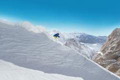 Man skier running downhill - stock photo
