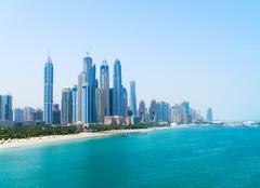 Beautiful sandy beach and modern metropolitan skyline - stock photo