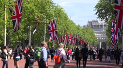 Pedestrians walk on the Mall near Buckingham Palace, London with British flags Stock Footage