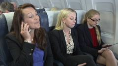 Female business team on plane get positive good news phone call Stock Footage
