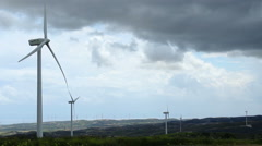 Time-lapse of wind turbine propellers rotating in green field, dark cloudy sky Stock Footage