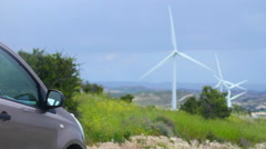 Electric car, wind turbines rotating, green energy source, clean environment Stock Footage
