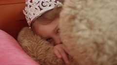 A little girl wearing a tiara hides her face behind a stuffed animal Stock Footage