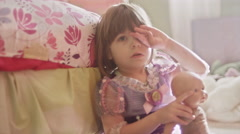 A sad little girl sits on the floor in her bedroom and rubs her eyes - stock footage