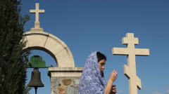 Woman crossing herself, praying, asking God for help and blessing, stone cross Stock Footage