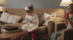 Two sisters sit down to watch TV, while one of them is wearing a dress and tiara Stock Footage