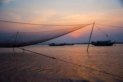 Calm scene of fishing net against purple sunset Stock Photos