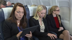 Bad news E-mail for female business team on plane Stock Footage