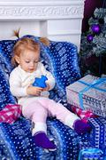 Cute little girl and gifts near Christmas tree. - stock photo