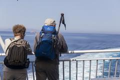 Stock Photo of Tourists on the deck of a ship heading to Santorini island, in Greece.
