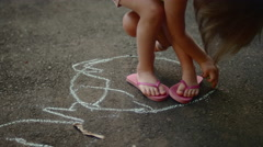 A little girl drawing a circle around her feet with chalk - stock footage