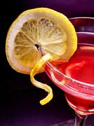Part of pomegranate drink with lemon on black background - stock photo