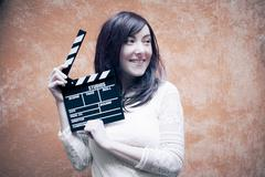 Young woman in 70s hippie style smiling with clapperboard Stock Photos