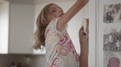 A girl pulls lollipops down from the kitchen cupboard - stock footage