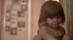 A little girl in a hallway putting her shoes on Stock Footage