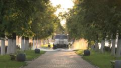 Morning in the city.Car drives down the alley .Watering the road. Stock Footage