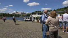 Tourists waiting near a boat anchored on the riverside in Prague Stock Footage