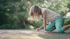 A little girl drawing on pavement with chalk - stock footage