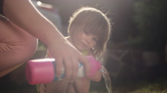 A little girl watches as somebody pours bubble soap - stock footage