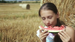 Girl eat watermelon near the haystack Stock Footage