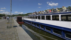 Tourists relaxing on Classic River boat on the riverside in Prague Stock Footage