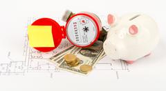 Water meter with piggy bank and coins on draft - stock photo