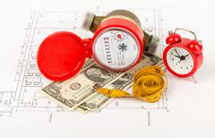 Water meter with tape-measure and alarm clock - stock photo