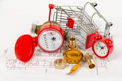 Water meter with shopping cart and pipe fittings - stock photo