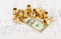Pipe fittings with dollars on draft - stock photo